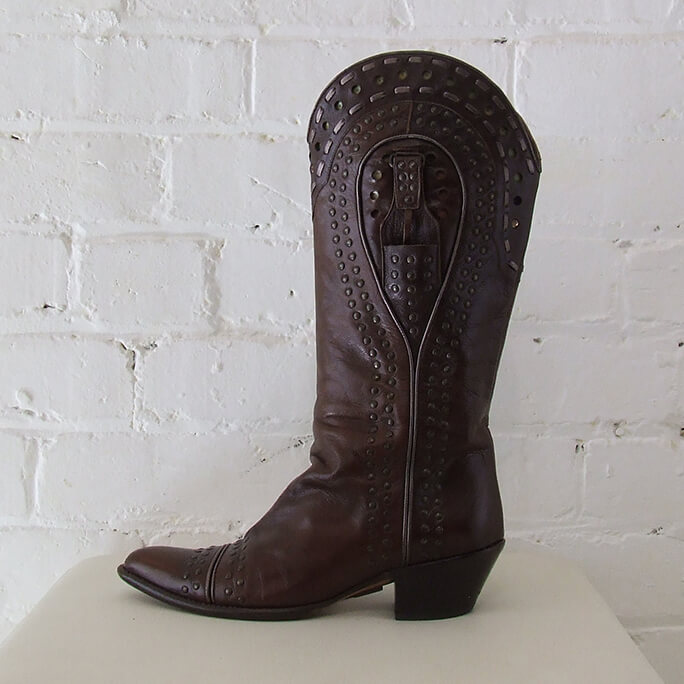Brown leather cowboy boots with rivets.