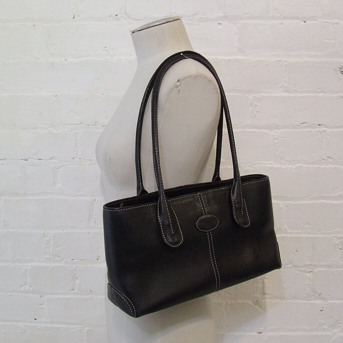 Black textured leather shoulder bag with white contrast stitching.
