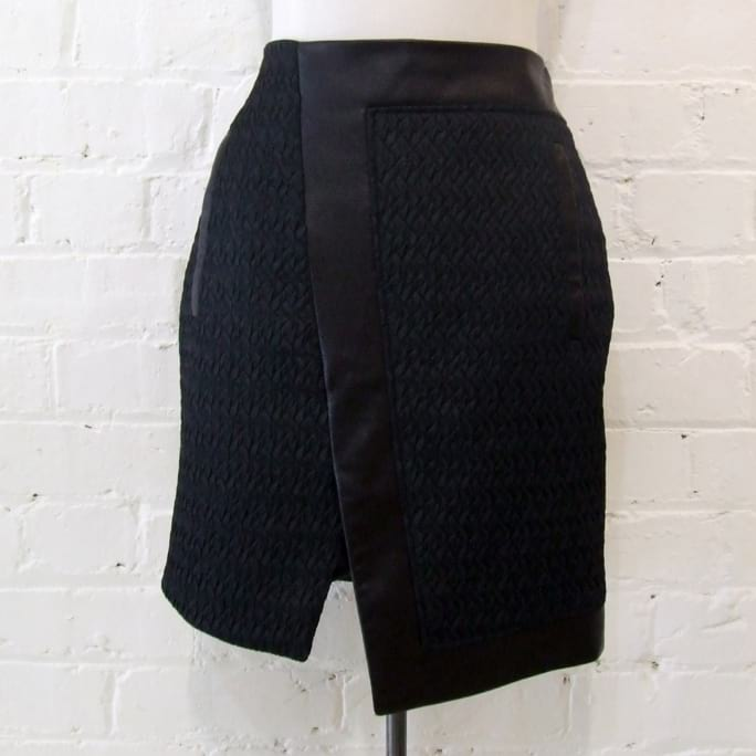 Assymetric mini skirt, synthetic quilting with leather trim and zip pockets.