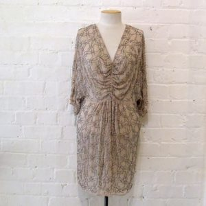Beaded mini dress with gathered front and bat sleeve.