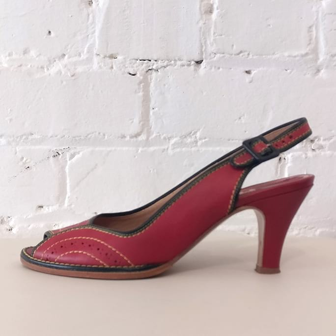 Red leather peep-toe sandal with ankle strap and contrast stitching.