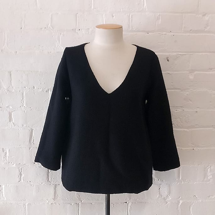 Lined woven wool v-neck top with 3/4 sleeve.