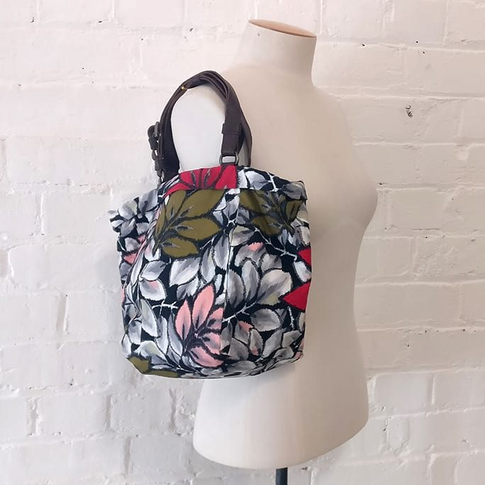 Cloth bag with floral print, has adjustable leather straps.