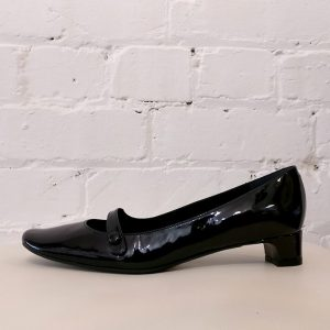 Patent leather mid-heel shoe with strap.