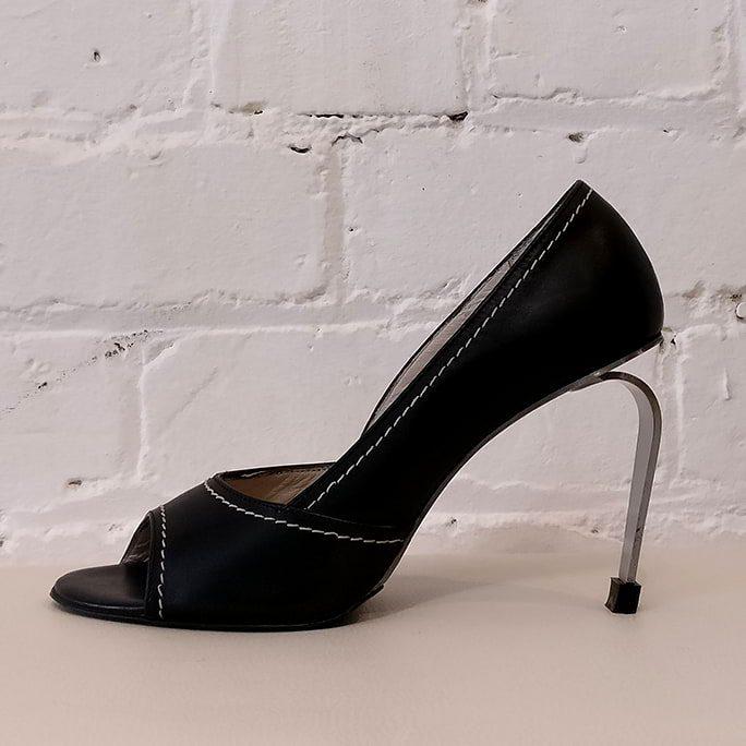 Leather peep-toe shoe with brushed steel heel.