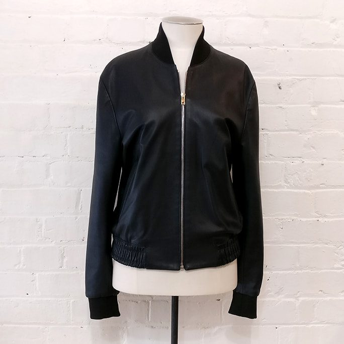 "Black bomber-style leather jacket with ""artist stripe"" lining."