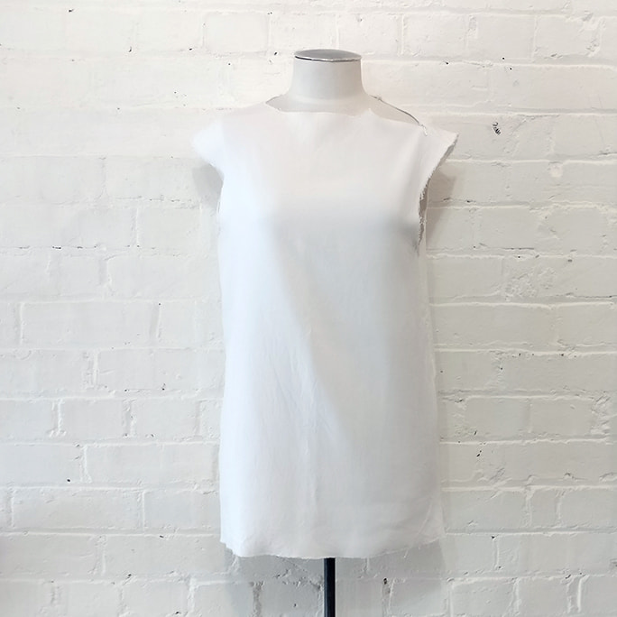 White top with deconstructed edges and zips.