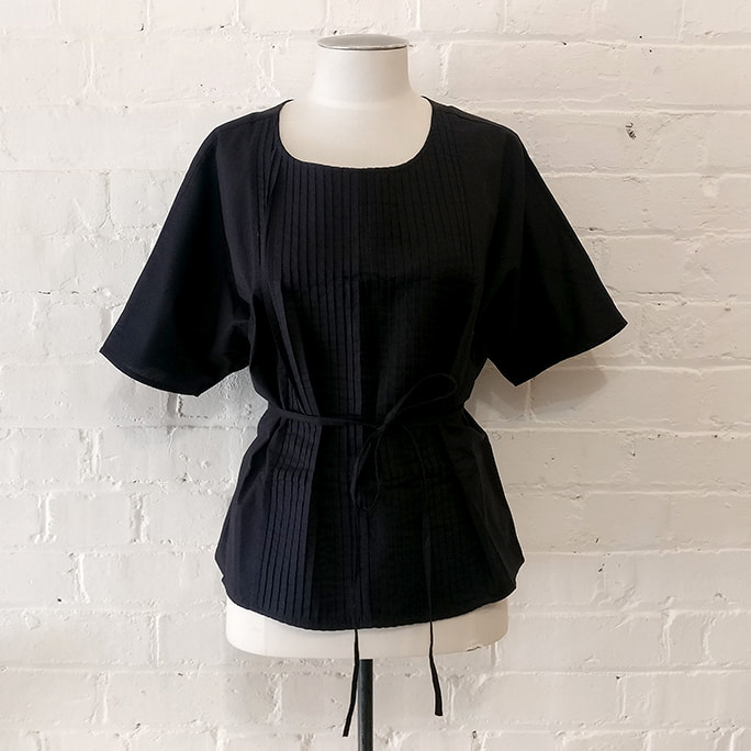 Black top with pintuck front and belt.