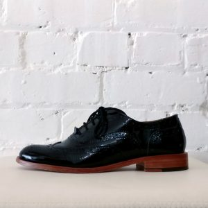 Patterned patent leather brogue.