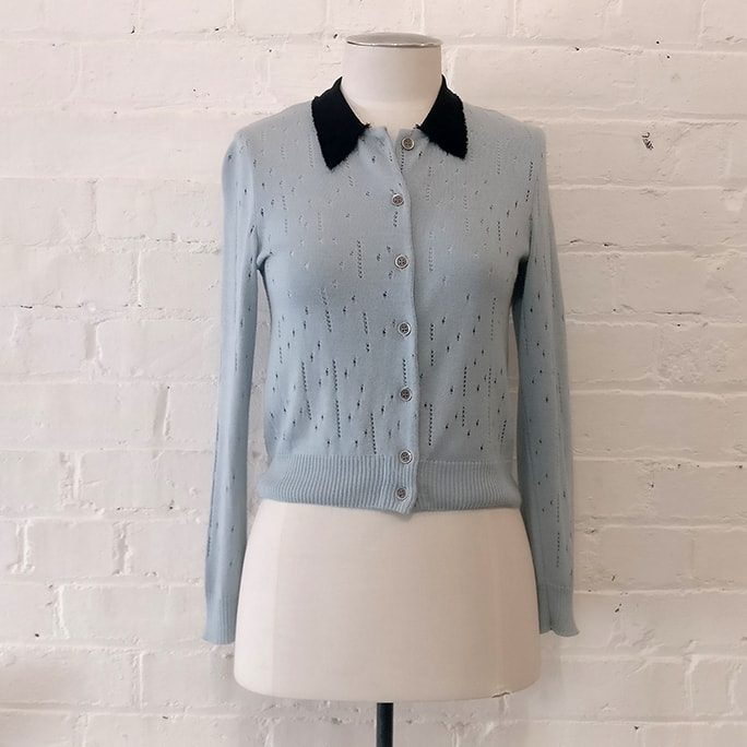 Pale blue cardigan with raw edge collar.