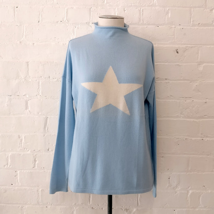 Pale blue cashmere rollneck sweater with star.