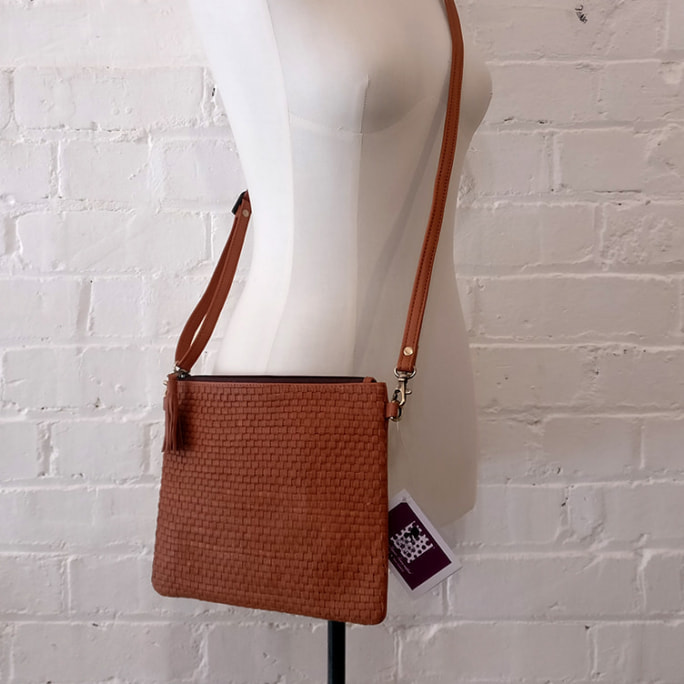Cross-body bag with detachable shoulder and clutch straps.