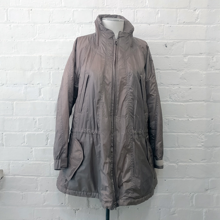 Showerproof rain jacket with concealed hood and multiple pockets, fully lined.