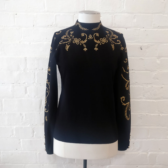 Gold embroidered high-neck top.