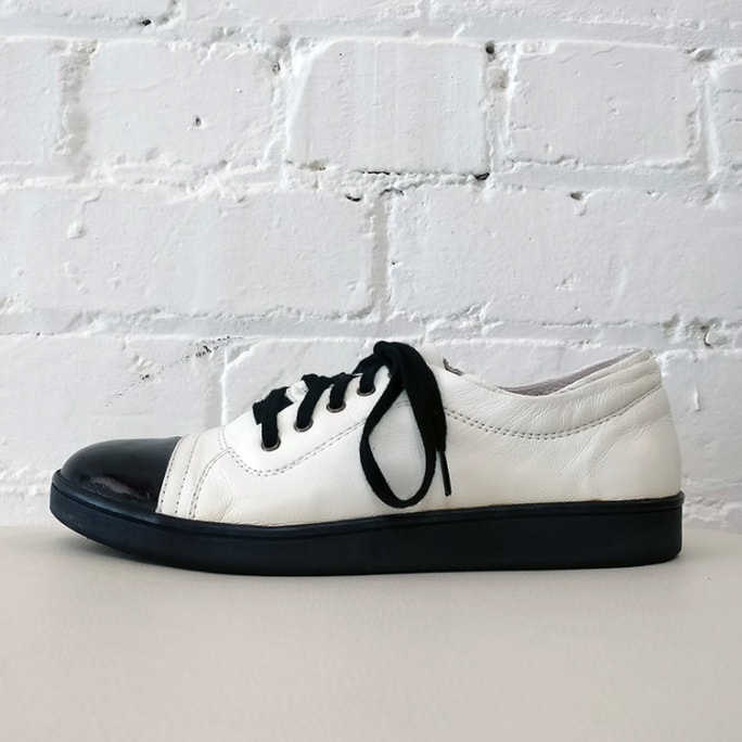 Black and white leather sneakers with patent toe.