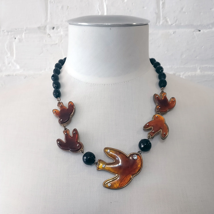 Neck piece with enamel birds and black beads.