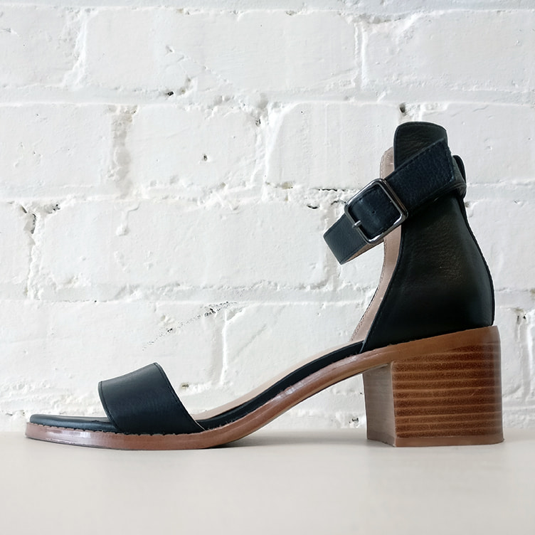 Black leather sandal with ankle strap.