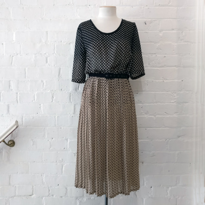 Short sleeve dot print dress with pleated skirt and black fabric belt.