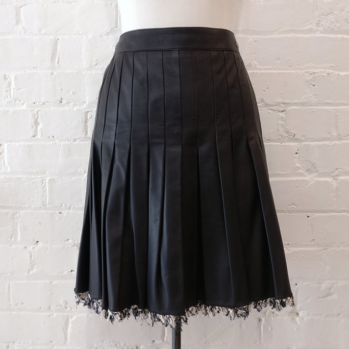 Black pleated lambskin skirt, silk lined, with signature Chanel fabric edging.
