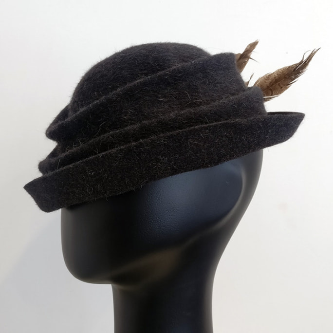 Grey wool sculpted hat with feather flourish.