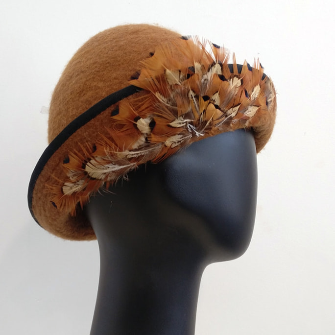 Light tan wool hat with feather detail.