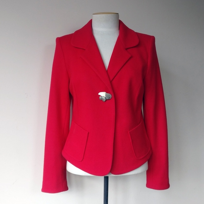 Lined cropped jacket with pewter fastening and patch pockets.