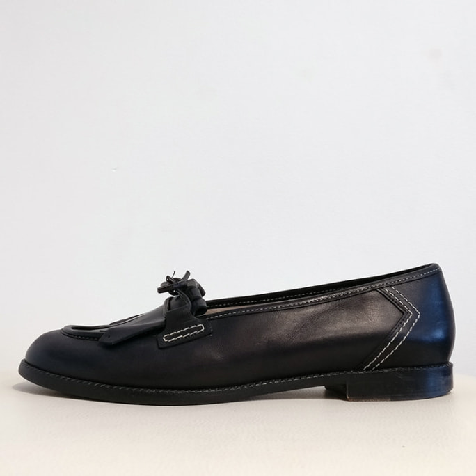 Round toe fringed loafer with contrast stitching.